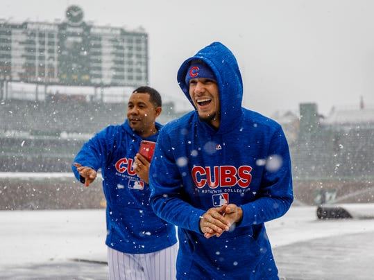 Chicago Cubs second baseman Javier Baez, front, plays in the snow at Wrigley Field in Chicago, Monday, April 9, 2018. The Cubs baseball game against the Pittsburgh Pirates was postponed a day because of snow that covered much of Wrigley Field, creating a scene more reminiscent of January than April. (Brian Cassella/Chicago Tribune via AP)