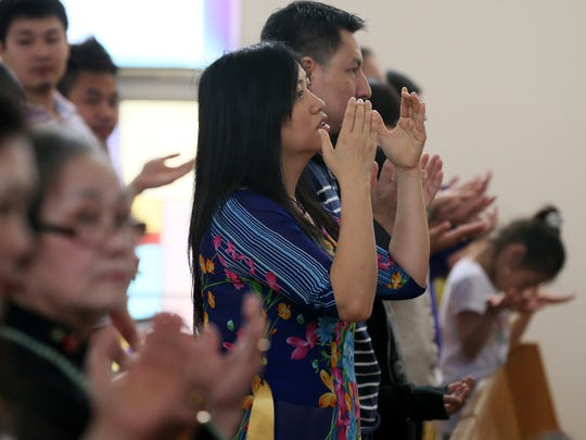 Tina Tran celebrates Easter with her congregation at Church of St. Peter Vietnamese Catholic Community . Sunday, April 20, 2014.