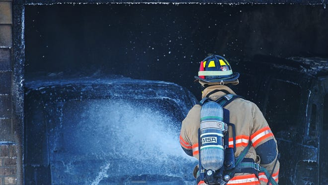 Firefighters with Sioux Falls Fire Rescue battle a garage fire Friday, Jan. 15, 2016, in southwest Sioux Falls. There were no injuries in the fire.