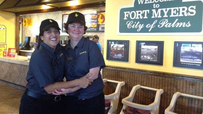 Franchisees Rusti Clinger, left, and Mari Mahan hug in excitement Monday at the grand opening of their first Zaxby's restaurant.