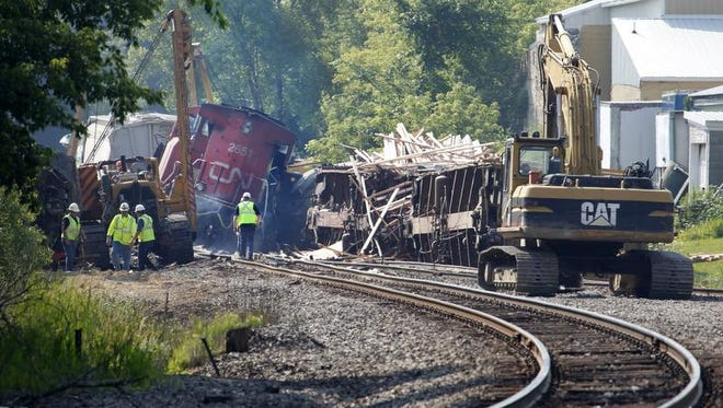 Workers clean up after a train derailment in Slinger.