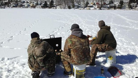 Fisherman wait for the barbeque while ice fishing at Lake Hopatcong.