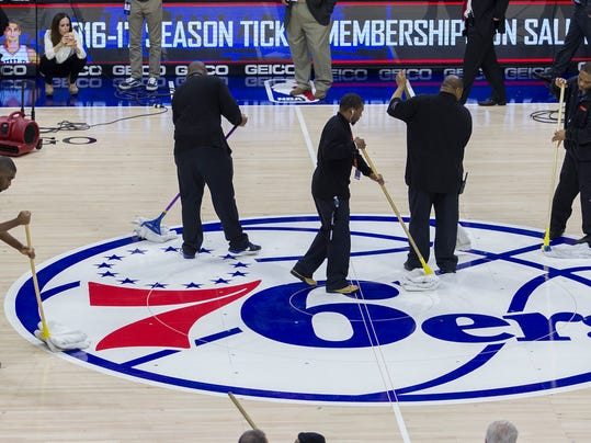Workers try to dry the court before an NBA basketball game between the Philadelphia 76ers and the Sacramento Kings was postponed, Wednesday, Nov. 30, 2016, in Philadelphia. The Philadelphia Flyers hosted an NHL game at the arena Tuesday night and the ice surface remained under the basketball court - standard procedure at the Wells Fargo Center. However, Wednesday was an unseasonably warm, humid day for late November in Philadelphia, and it likely affected the surface. (Charles Fox/The Philadelphia Inquirer via AP)
