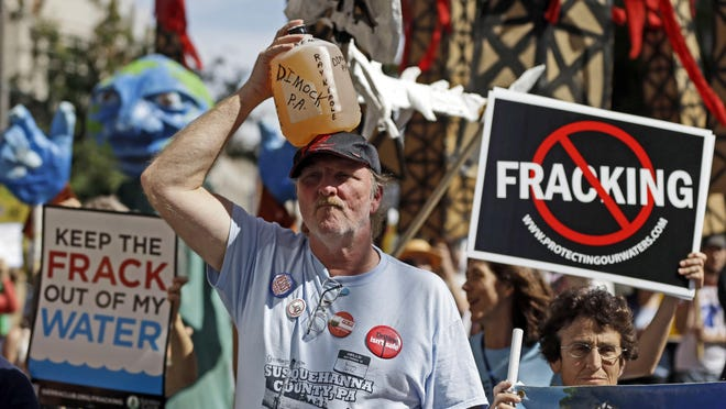 Matt Rourke/AP Ray Kemble of Dimock, Pa., is among those protesting fracking at a demonstration in Philadelphia in 2012. Amid ongoing complaints about the quality of drinking water, government scientists are collecting water and air samples in Dimock. FILE – In this Sept. 20, 2012 file photo, Ray Kemble, of Dimock, Pa., holds a jug of his well water on his head while marching with demonstrators against hydraulic fracturing outside a Marcellus Shale industry conference in Philadelphia. Federal government scientists are collecting water and air samples in the first week of August 2017 from about 25 homes in Dimock, Pa., a tiny, rural crossroads about 150 miles north of Philadelphia that became a flashpoint in the national debate over fracking to investigate ongoing complaints about the quality of the drinking water. (AP Photo/Matt Rourke, File)