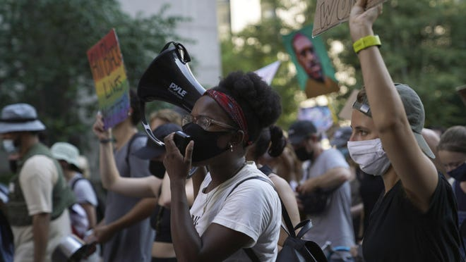 Kianna Ruff, left, and Erin Hancock, right, two activists who met in seminary, protest against racial injustice and police brutality July 26, 2020, in Manhattan, New York. Many involved in the demonstrations that erupted after George Floyd's killing say they deepen spiritual connections and embody familiar elements of traditional faith.