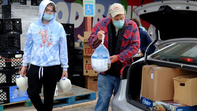 Aaron Isham, left, and Jack Hunt join other River Valley Regional Food Bank volunteers and staff, Saturday, Nov. 21, loading Thanksgiving meals for more than 350 area families.