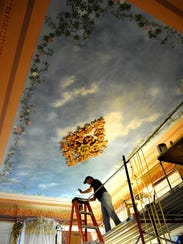 Artist Phil Carroll takes care of painting decorations