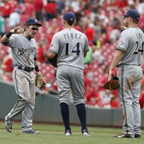 Milwaukee Brewers second baseman Scooter Gennett (2) celebrates with teammates Hernan Perez (14), and Adam Lind (24) following their 6-1 win over the Cincinnati Reds on Sunday.