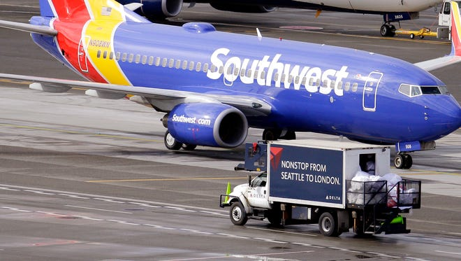 "A Southwest plane is pictured at Seattle-Tacoma International Airport. On Tuesday, a video showed police officers removing a woman from a Southwest plane as she frantically asked, ""What are you doing?"""