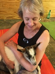 Cathy Levinson, of Greensboro, holds a baby goat after