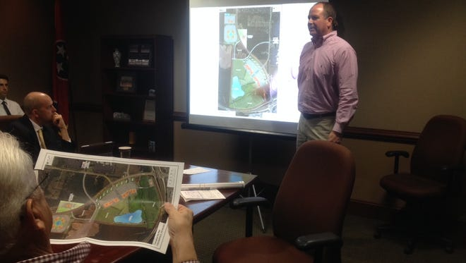 Kevin Vaughan presents a new shopping center development concept to members of Collierville's Board of Mayor and Aldermen. Alderman Tom Allen, left, holds a copy of the development map.