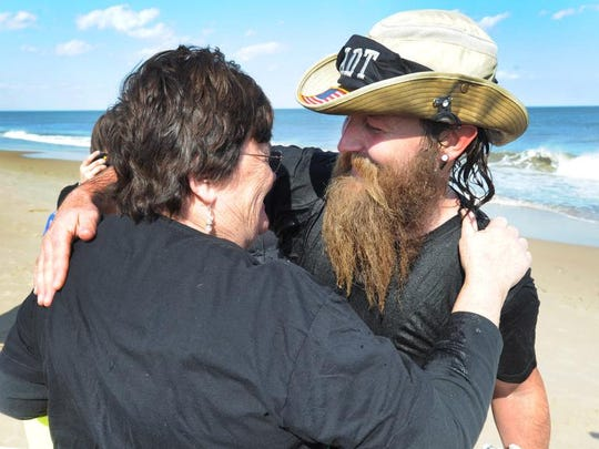 Josh Seehorn gets a hug from his mother Terry Seehorn, of Toccoa, Ga., after he completed his 4,800-mile hike across the American Discovery Trail at Cape Henlopen State Park Saturday.