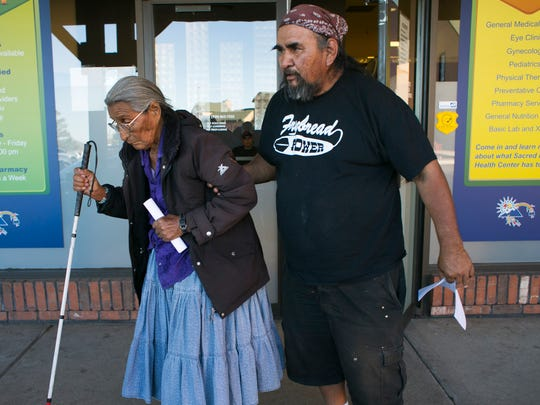 Milton Yazzie,  57, assists his mother, Della Yazzie, 83, who is partially blind, after Milton had a medical check-up at the Sacred Peaks Health Center in Flagstaff. Milton has diabetes and pancreatitis, which along with Della's blindness could be related to uranium exposure from living among abandoned uranium mines. In 2005, three other family members have died from kidney cancer or failure.