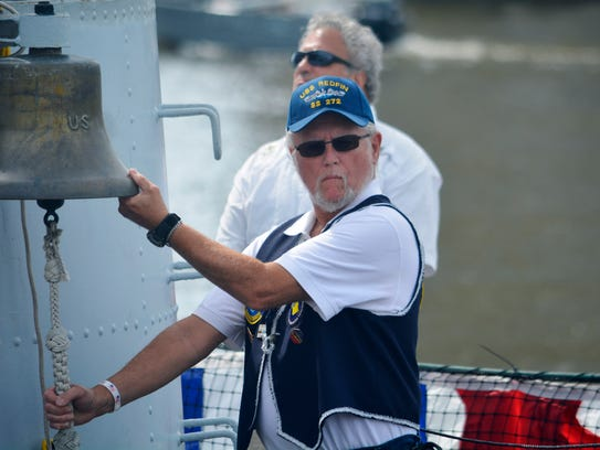 Al King rings the bell on the deck of the USS Cobia