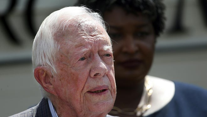 Former President Jimmy Carter speaks in September as Democratic gubernatorial candidate Stacey Abrams listens during a news conference to announce her rural health care plan, in Plains, Ga. Carter is now the longest-living president in American history.