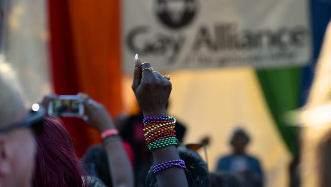 Festival goer raises a beaded fist at Pride Fest 2016.