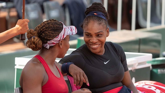 Venus Williams (left) and Serena Williams share a moment during their doubles match against Andreja Klepac and Maria Jose Martinez Sanchez during the 2018 French Open at Roland Garros on June 3.