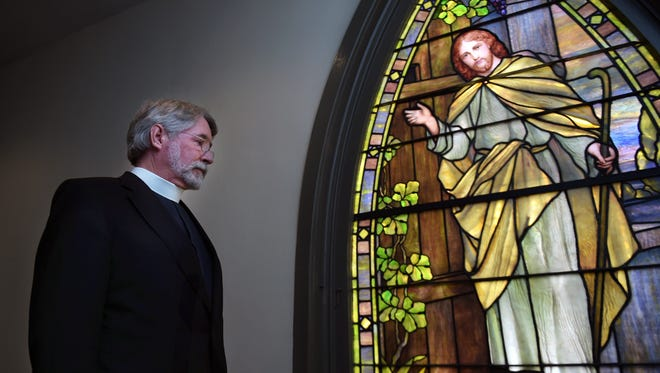 The Rev. William Barton of St. Paul's Episcopal Church stands next to a stained-glass window depicting Jesus at an open door. St. Paul's Episcopal is open 24/7 for people to pray and meditate.