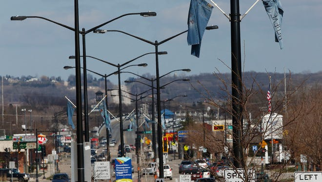 Jeans hang from poles on West Johnson Street Tuesday April 12, 2016.