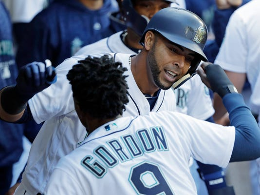 Seattle Mariners' Nelson Cruz, right, celebrates with Dee Gordon in the dugout after hitting a two-run home run against the Cleveland Indians during the sixth inning of a baseball game, Saturday, March 31, 2018, in Seattle. (AP Photo/Ted S. Warren)