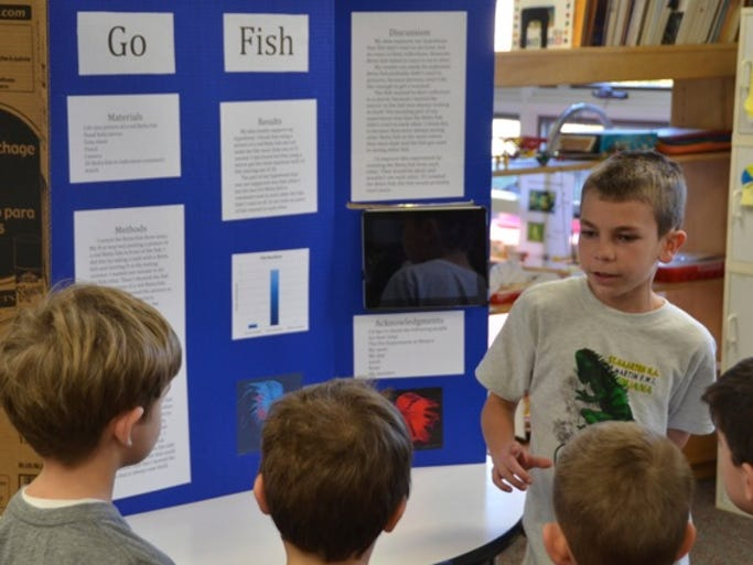 Children's Meeting House Montessori School fifth-grader Alex Eicher explains his science fair project to a group of younger children. Eicher examined aggressive behavior in male Betta fish and the factors that control it.