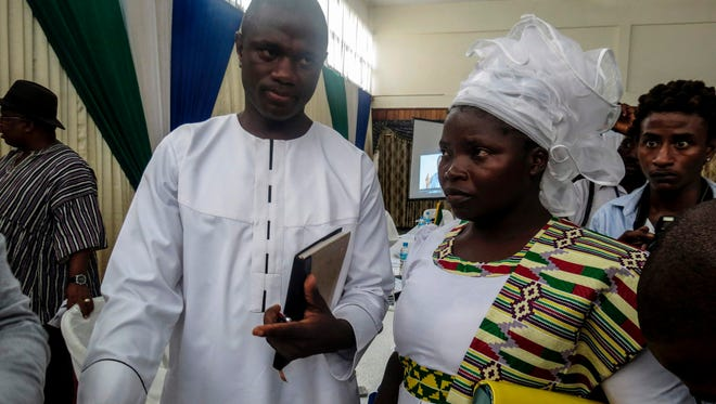 Pastor Emmanuel Momoh arrives with his wife on May 11, 2017, in Freetown, Sierra Leone, for the auction of the 709-carat diamond he found earlier this year.
