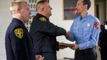 Mike Deising, former president of the St. Clair County Firefighters Association and a Marysville firefighter, presents Port Huron firefighter Tim Oleaga a Meritorious Unit Citation Friday, March 24, 2017 at the Port Huron Fire Department central station. Members of the Port Huron Fire Department's Shift B were given the award for their role in saving a Canadian man who had climbed over the railing of the Blue Water Bridge in Feb. 2016.