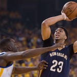 New Orleans Pelicans forward Anthony Davis (23, right) shoots the basketball against Golden State Warriors forward Draymond Green (23, left) during the first quarter in Game 2 of the first round of the NBA Playoffs at Oracle Arena last spring.