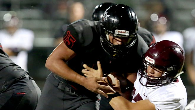 North Salem's Rigo Padilla (15) is dragged down by Forest Grove's Drake Littlefield (27) in the second half of the Forest Grove vs. North Salem football game at North Salem High School on Friday, Sept. 8, 2017. Forest Grove won the game 13-6.