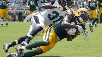 Green Bay Packers wide receiver Davante Adams (17) makes a touchdown catch in front of Jacksonville Jaguars cornerback Davon House (31) during the first half Sunday, Sept. 11, 2016.