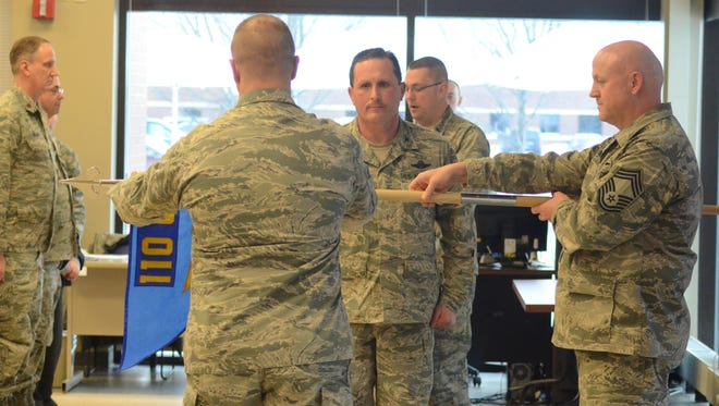 Col. Bryan Teff, facing, Chief Master Sgt. Herbert Ward, right, and Maj. Daniel Guy, facing Teff, activate the Cyber Squadron.