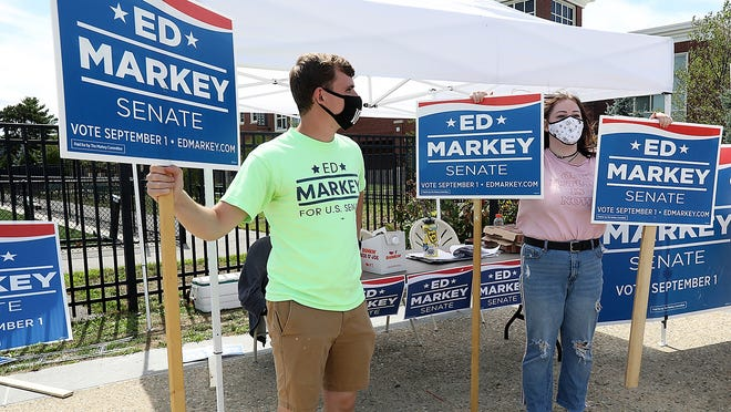 Chris Cantwell of Marshfield and Peyton Kennedy hold signs for Ed Markey while campaigning for the senator at the high school on Tuesday, Sept. 1, 2020.