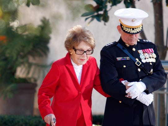 Former first lady Nancy Reagan is helped by Marine