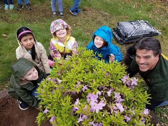 Students planting with shade tree committee member