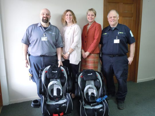 EMTs from Rural/Metro accept new car seats from First Heritage Federal Credit Union. From left: Curtis Mason, EMT-P, Julie Monahan, business development officer, Chris Panosian, community development officer, and Doug Reed, EMT-B.