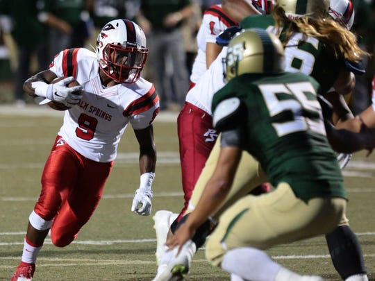 Palm Springs' Franklin Miller carries the ball for a gain to allow him to score against Tahquitz High in the next play in the 1st quarter on August 28.