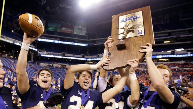Fort Wayne Dwenger's Colin Burns (40), Nick Fiacable (24), Zack Norton (21) and Noah Freimuth (45) celebrate after Fort Wayne Bishop Dwenger defeated East Central, 27-3, in an IHSAA Class 4A state championship football game , Nov. 28, 2015.