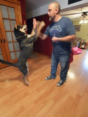 Bob Meyer does a high-five with Homer, the dog the family adopted from Bonnie's Animal Rescue Kingdom in Paramus last September. Homer was one of the pups chosen to play in Animal Planet's Puppy Bowl XIII, which airs on Super Bowl Sunday.