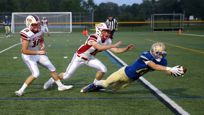 Webster Schroeder receiver Mike Masucci (10) dives into the end zone behind Hilton's Joey Lipani (18) and Ryan Butts.