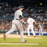 Chicago White Sox Tyler Flowers gets ready to slap hands with 3rd base coach Joe McEwing as he rounds the bases with a two run home run off Detroit Tigers Kyle Lobstein, back center, in the second inning of their 2-0 win over the Detroit Tigers in Detroit on Monday, September 22, 2014.