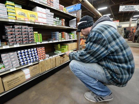 Dustin Valley of Green Bay shops for ammunition Thursday at Gander Mountain in Howard. Valley said he plans to use the ammo during today's gun-deer season opener.