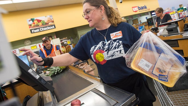 Kathy Normann rings up groceries Tuesday at King Soopers at 2602 S. Timberline Road in Fort Collins. Depending where they shop and what they buy, Northern Colorado consumers may pay more in sales taxes and fees on their purchases.