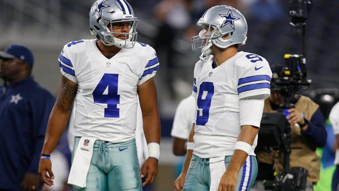 Dallas Cowboys quarterback Dak Prescott (4) and quarterback Tony Romo (9) talk during the pregame warmups against the Miami Dolphins at AT&T Stadium.