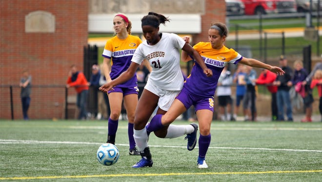 Brebeuf Jesuit's Kayla Fitts shields the ball from a Guerin Catholic defender during the Braves' regional final win over the Golden Eagles.