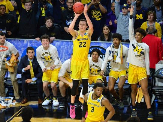 Michigan guard Duncan Robinson hits a three-point basket