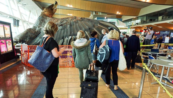 Passengers make their way around a giant eagle sculpture promoting 'The Hobbit' movie trilogy which fell from the roof in the wake of a 6.3 magnitude earthquake at Wellington Airport on Jan. 20, 2014.