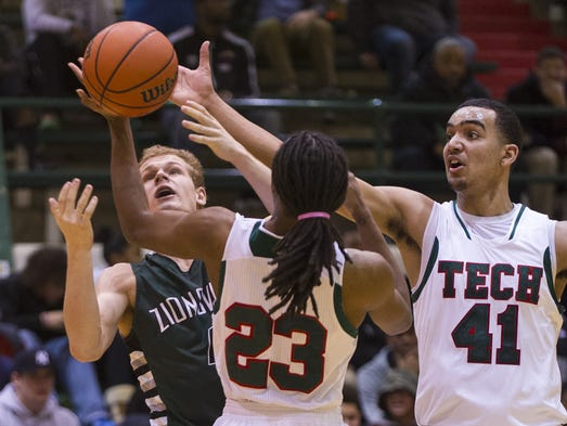 Zionsville High School sophomore Jack Pilcher (4) looses control of the ball as Arsenal Tech High School senior Michael Jones (23) and senior Trey Lyles (41) try to pull it in during the first half of boys varsity basketball action, Friday, Feb. 21, 2014, at Arsenal Technical High School.