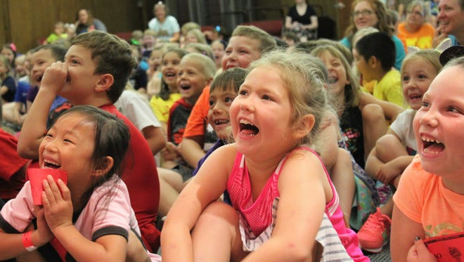 Ryann, center, and her friends from a summer kids' program at Beltway Park Church laugh out loud at the antics of clowns Slappy and Monday at Tuesday's Young Audiences program at the downtown Abilene Public Library.