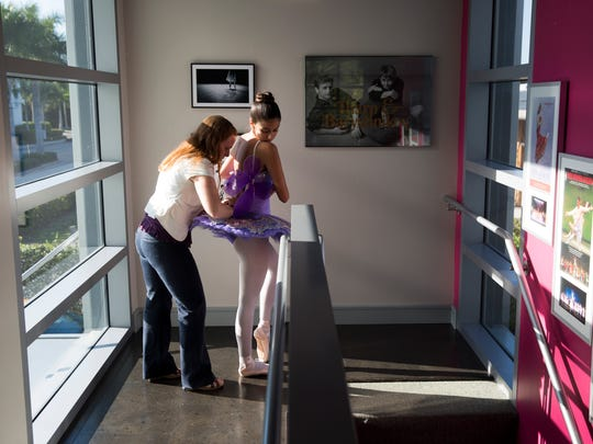 """Jessica Painter, Production Coordinator for the Naples Ballet upcoming performance """"Sleeping Beauty"""", assists Jessica Garciduenas, 16, with tying up her costume prior to rehearsal Monday, May 8, 2017 in Naples."""