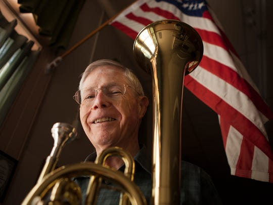 Bob Moody, director of the Stonewall Brigade Band, stands for a portrait with a replica saxhorn, the instrument used at the founding of the group in 1855, inside the band's building in Staunton on Wednesday, May 13, 2015.